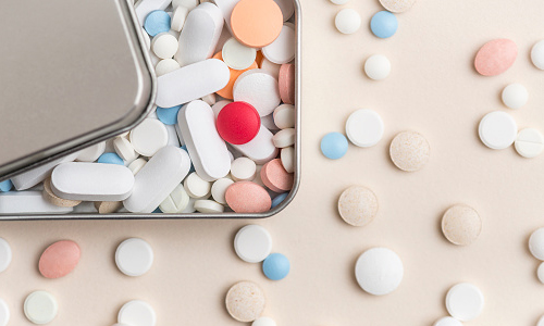 Colorful pills and tablets in metal drug box